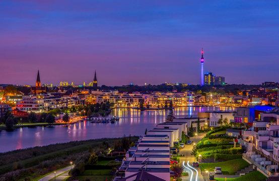 Amazing panoramic view of Phoenix Lake in Dortmund, Germany over city skyline and Florian Tower illuminated at twilight