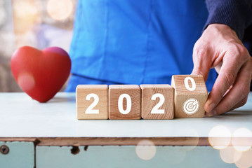 Doctor hand flip over wood block with New year 2020 and goal icon healthcare, achieving new goals in the new year.