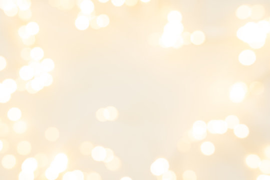 Frame of defocused Christmas lights on white wooden background. Christmas and New Year holidays celebration concept