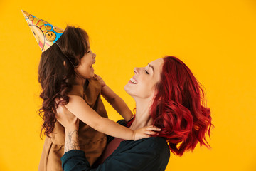 Image of caucasian happy woman lifting up her daughter in arms