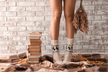 Young woman with stack of books standing on plaid near brick wall