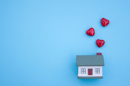 A small house, three hearts fly out of the pipe on a blue background. The concept of buying, selling, renting real estate, mortgages, happiness in your homeю Place for text