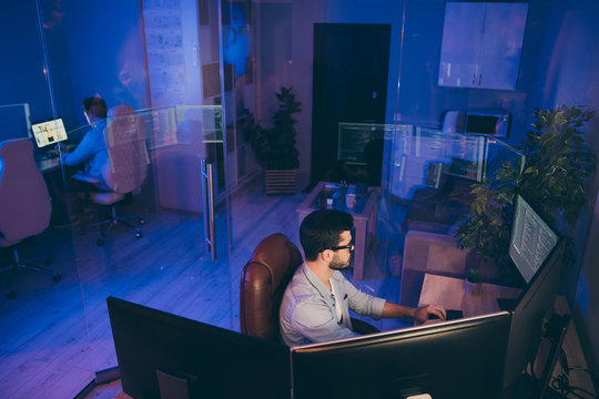 Profile photo of it specialist guy sitting chair work late at night seriously looking monitors writing secure code for website server content development expert night office indoors