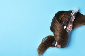 Wall Mural - Spray bottle wrapped in lock of hair on light blue background, flat lay with space for text. Natural cosmetic products