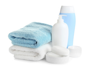 Wall Mural - Folded soft towels and toiletries on white background