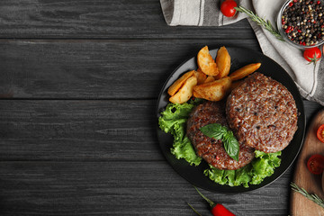 Flat lay composition with grilled meat cutlets for burger on black wooden table. Space for text