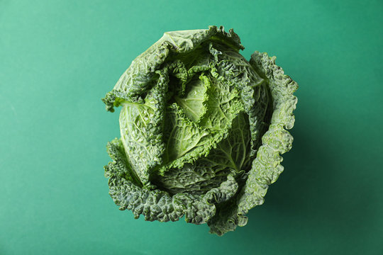 Fresh savoy cabbage on green background, top view