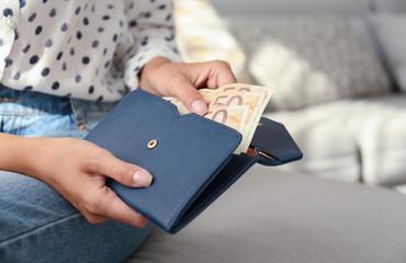 Woman putting Euro banknotes in wallet, closeup