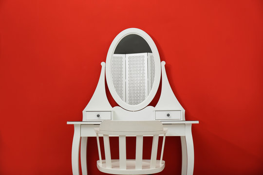 Elegant white makeup table and chair on red background