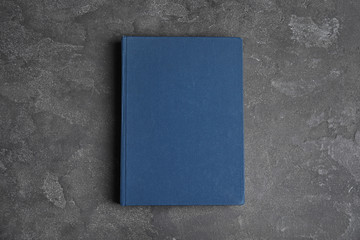 Hardcover book on grey stone table, top view. Space for text