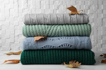 Fototapete - Stack of warm clothes and autumn leaves on white wooden table against textured wall