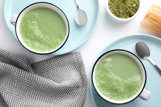 Flat lay composition with tasty matcha green tea latte on white table