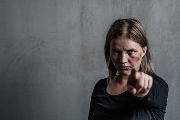 Portrait of a woman victim of domestic violence and abuse which pointing finger at you. Empty space for text
