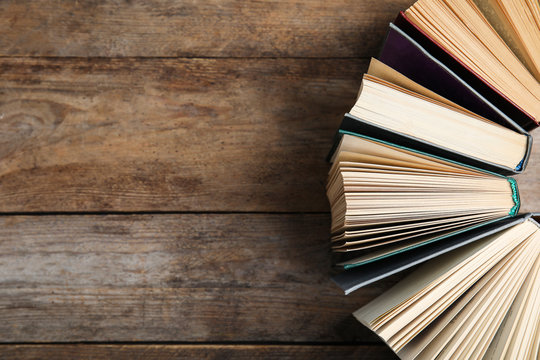 Hardcover books on wooden background, flat lay