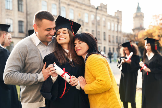 Happy student with parents after graduation ceremony outdoors