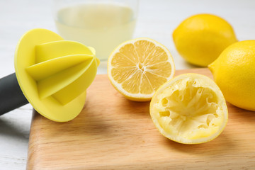 Citrus juicer and squeezed lemon on wooden board