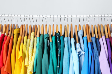 Rack with bright clothes on light blue background. Rainbow colors