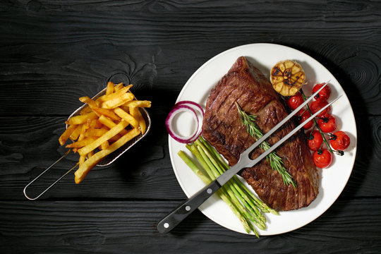 grilled steak on a plate with asparagus and tomatoes, French fries and country potatoes. Three different sauces: ketchup, mustard and barbecue on a dark wooden background, top view, horizontal photo