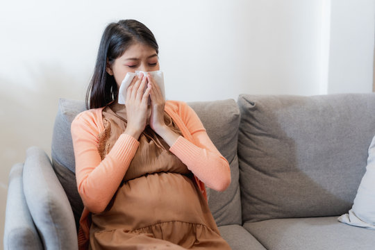 Young Asian pregnant woman have suffering from flu and sneeze, runny nose, stuffy nose and then her blow nose using a tissue