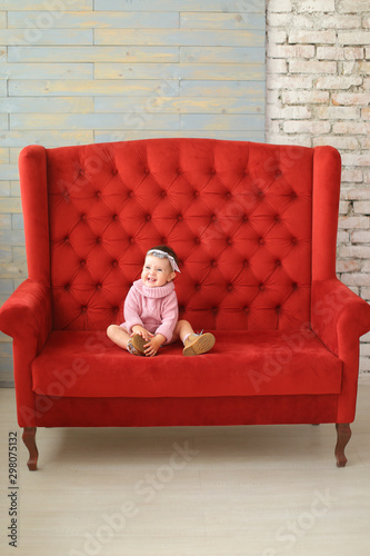 Phenomenal Little Girl Wearing Pink Sweater Sitting On Red Sofa Stock Bralicious Painted Fabric Chair Ideas Braliciousco