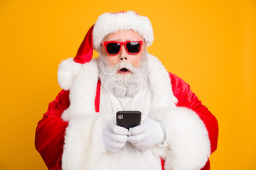 Omg tradition christmas discounts. Close up photo of impressed voiceless funky fat santa claus use smartphone find x-mas sales on internet wear red hat headwear isolated over shine color background