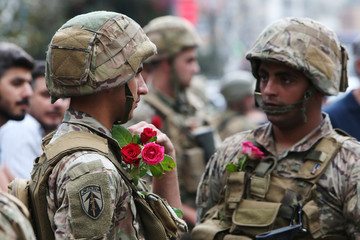 Army soldiers wear roses given by demonstrators during an anti-government protest in Nabatiyeh