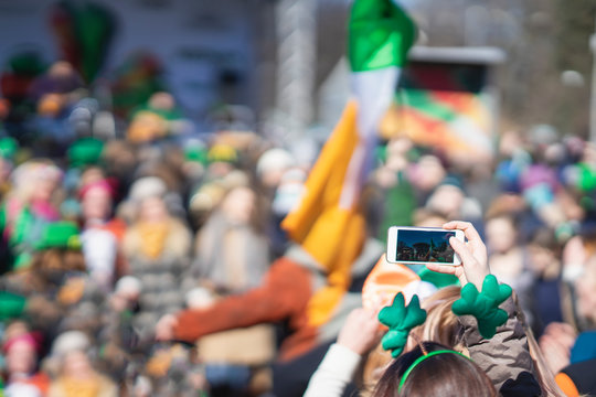 Hands of girl with mobile phone, making photo of carnival of St. Patrick's Day, traditional carnival party on a smartphone