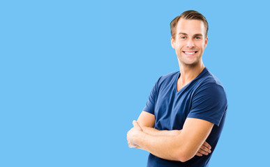 Portrait of young handsome smiling man wearing in casual smart blue clothing, with crossed arms. Blue color background, with copy space for some text. Caucasian male model at studio picture.