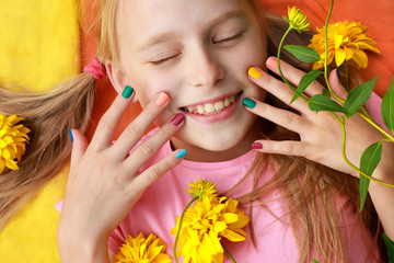 Bright and colorful children's manicure on the nails of girls with yellow flowers and good mood.