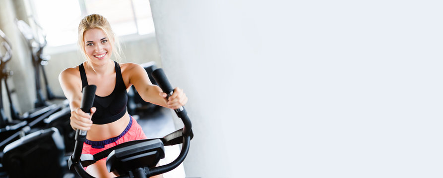 Women wearing sportswear doing workout activity, spinning an electric bicycle in the gym For good health Have a beautiful shape And allowing the muscles to relax. copy space on banner background.
