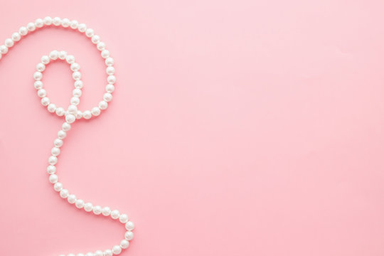 Pearls on pastel pink background