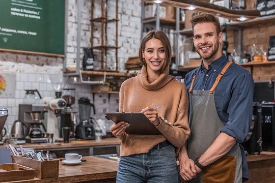 Small business smiling partners standing together at their coffee shop