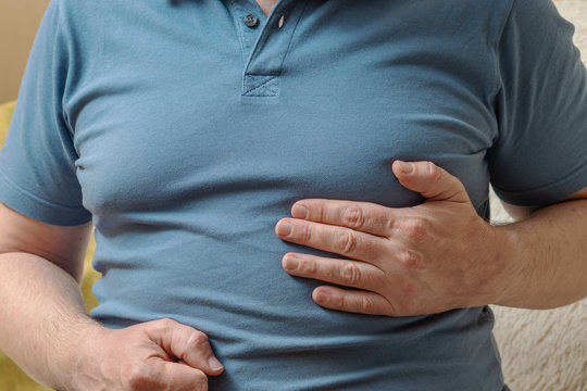 A man in a blue T-shirt holds his hands in his heart. Heart health problems