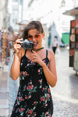 Confident woman in summer dress taking picture with camera while standing on scenic sunny city street