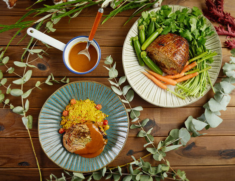 Overhead boneless and stuffed fried lamp leg served on plates with fresh vegetables and rice amidst green twigs on wooden table