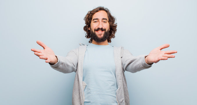 young bearded crazy man smiling cheerfully giving a warm, friendly, loving welcome hug, feeling happy and adorable against flat color wall