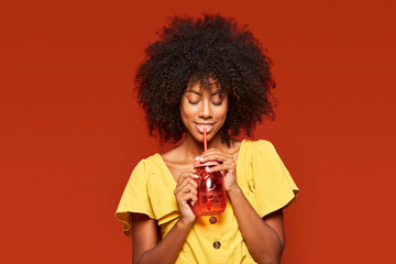 Dreamy young African American lady with curly hair holding red jar with straw and enjoying beverage on red background