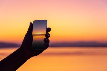 Faceless tourist holding smartphone with shot of beautiful orange sunset on blurred background