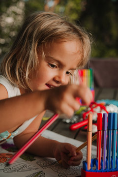 Focused little girl leaning on table and coloring pictures at book with marker pen on blurred background of room at home