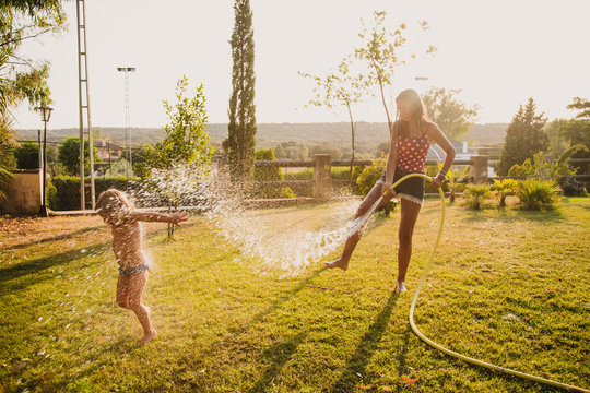 Full body cheerful teenager hosing little girl with clean water while having fun on lawn in yard together