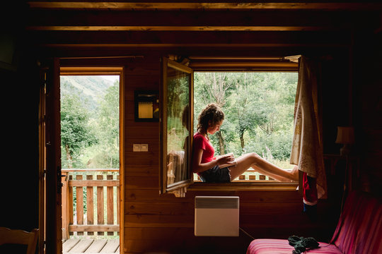 teen girl reading book in the window on a hot summer day