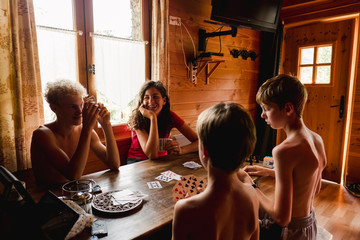 stock photo of four kids playing a game of cards in the summer in a chalet