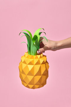 Paper whole pineapple with green leaves is holding a woman's hand on a coral background with copy space. Handcraft exotic fruit. Pantone 16-1546 Living Coral is the color of the year 2019.