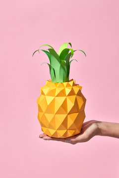 A woman's hand is holding a handcraft pineapple made with paper around a coral background with copy space. Pantone 16-1546 Living Coral is the color of the year 2019.