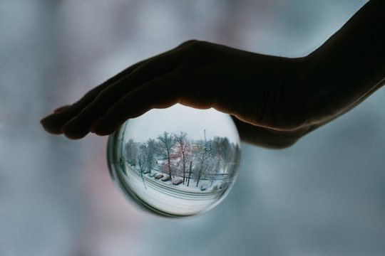 Crop hand holding sphere with winter landscape