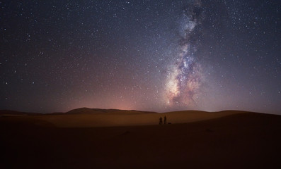 Silhouette of two photographers with night scene milky way background in the galaxy