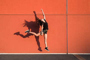 Woman jumping against a red wall