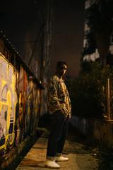 Black man standing near graffiti wall at night