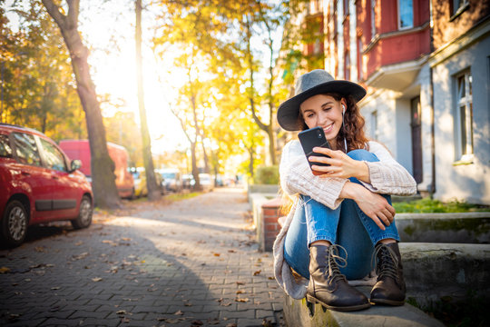 Beautiful stylish woman sitting on street at sunny day and using mobile phone with headphones