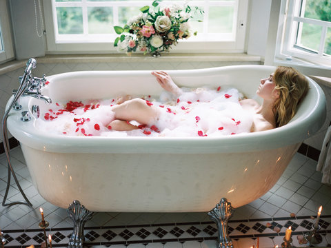 Relaxing woman in bath with burning candles near
